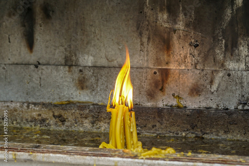 Flame of a bunch of burning candles standing in a container with a smoked wall Wallpaper Mural