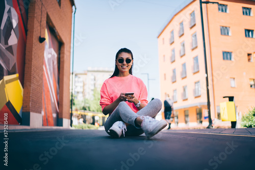 Toothy hipster girl in stylish sunglasses enjoying leisure for networking smartp Tapéta, Fotótapéta