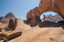 Woman Standing Under A Desert Rock Arch In Spitzkoppe, Namibia