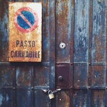 A No Parking Sign On A Grungy Metal Door In Italy.