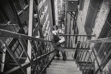 Retro Look Man In Suit Using Tablet In New York Old Building Fire Escape Stairs