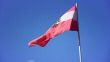 Austrian Flag Waving In The Wind On Sunny Day Against Blue Sky Austria. Flag Theme