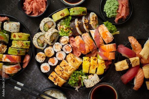 Asian food fest. Menu sushi with nigiri, maki, uramaki on black plates. Various kinds of sushi