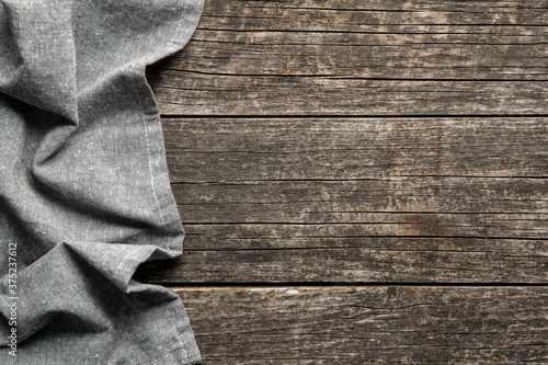Foto Folded tablecloth over antique wooden table.