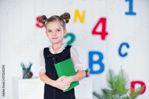 Photo Happy smart girl in school unifrom hold book and look at camera.