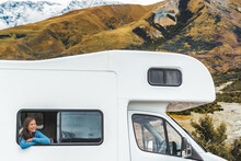 RV Road Trip Tourist Woman Looking Out The Window Of Her Motorhome On New Zealand Travel. Happy Young Asian Girl Traveling Outdoors In Adventure Vacation Driving A Campervan. Home Away From Home.