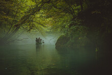 Back View Of A Green Canoe And People In A Misty And Foggy River Between The Trees. Scary Spooky And Mistery Exploration With A Canoe On A River Krupa In Slovenia.