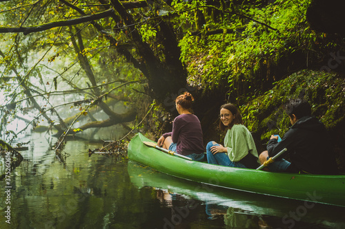 Photo Group of three people, two young caucasian women and a man exploring, paddling with green canoe in misty and cold water with fog and green background