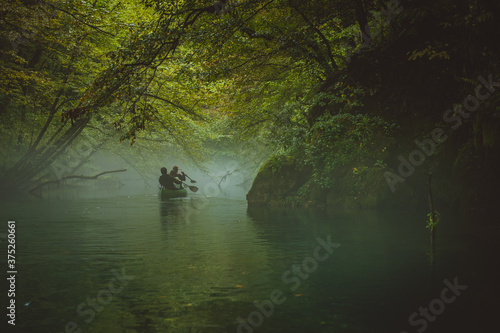 Back view of a green canoe and people in a misty and foggy river between the trees Canvas Print