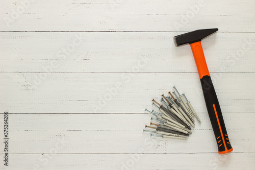 Photographie Hammer with a rubberized orange and black handle and stack of dowel nails on white wooden background