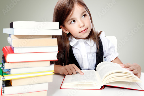 Photo Young cute girl sitting at the table and reading a book