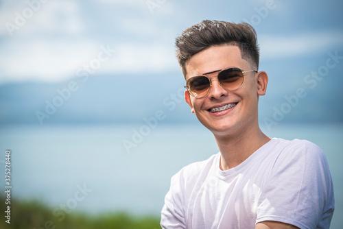 joven bronceado con lentes de sol en exterior Fototapet