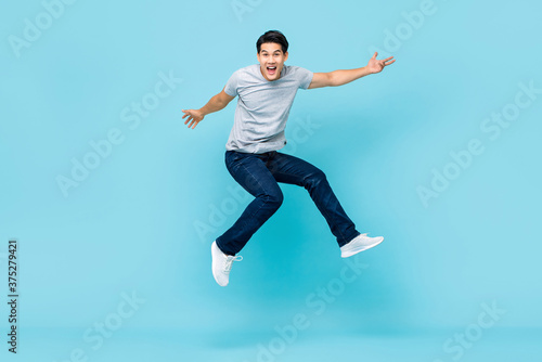 Fotografia Energetic happy young Asian man in casual clothes jumping studio shot isolated i