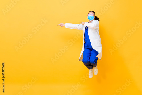 Asian female doctor wearing medical mask jumping and pointing hands to empty spa Poster Mural XXL