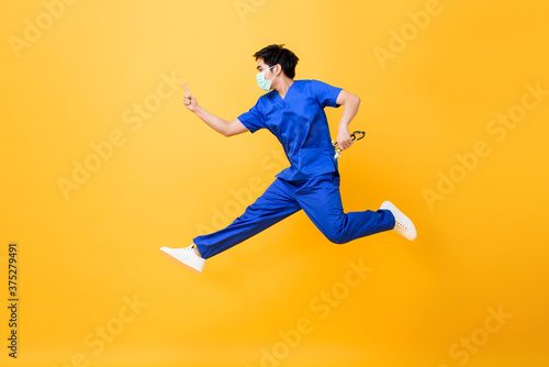 Fotografie, Obraz Young Asian male doctor wearing medical mask jumping and pointing hand up isolat