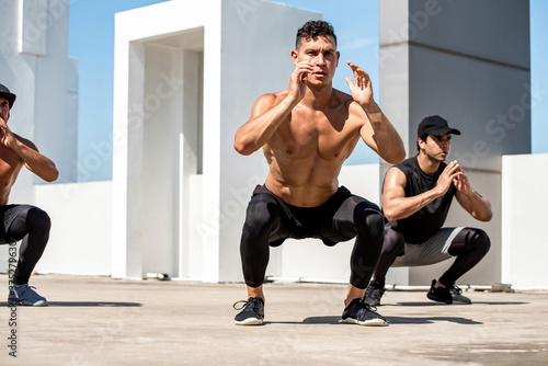 Fototapeta Group of fit sports men doing squat bodyweight workout training outdoors on buil
