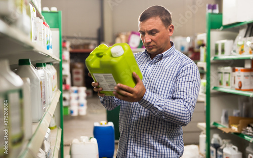 Foto Portrait of man holding plastic gallon with liquid contents in hypermarket