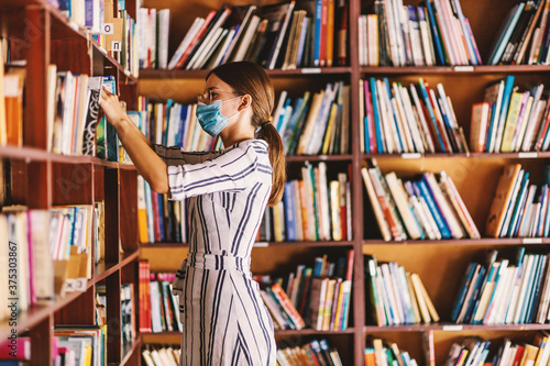 Young attractive librarian with face mask on searching for a book while standing in library during corona virus pandemic Fototapeta