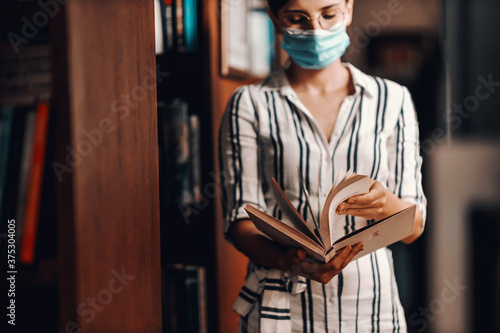 Valokuvatapetti Young attractive college girl with face mask on standing in library and browsing material in a book for school project during corona virus pandemic