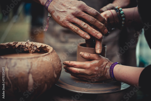 Valokuva close up of hands of a potter and his student learning pottery at throwing wheel outdoors