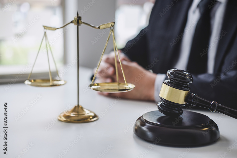Fototapeta Male lawyer or judge working with contract papers, Law books and wooden gavel on table in courtroom, Justice lawyers at law firm, Law and Legal services concept