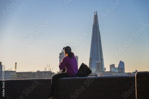Back view of a female sitting on river Thames embankment with The Shard in the b Wallpaper Mural