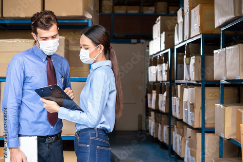 Two staff worker at warehouse wear surgical mask during work hour as new normal Fototapeta