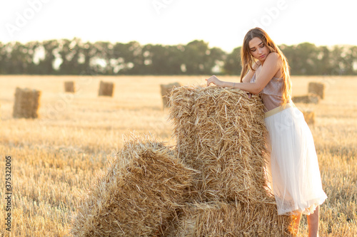 Obraz na plátně young woman lean on haystack walking in summer evening, beautiful romantic girl