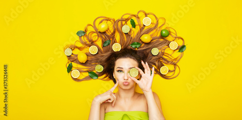 Fototapeta positive girl lying on yellow background with citrus fruits in long hair,young w