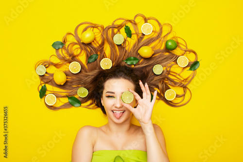 Photo cheerful positive girl lying on yellow background withlemons on long hair, young