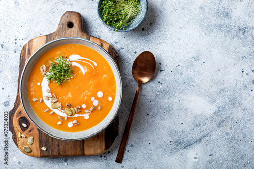 Foto Vegetarian autumn pumpkin and carrot soup with cream, seeds and cilantro micro greens