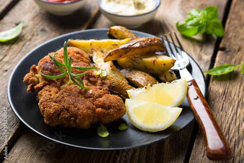 Fotografering Homemade breaded German Weiner schnitzel with potatoes and lemon