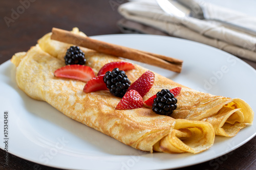 Appetizing crepes on white plate with strawberry and blackberry dressing. #375343458