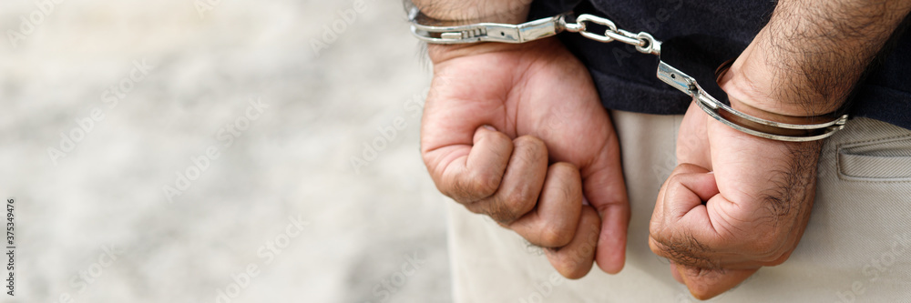 Fototapeta Prisoner male criminal standing in handcuffs with hands behind back. banner copy space.