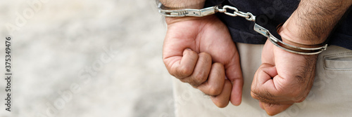 Fotografía Prisoner male criminal standing in handcuffs with hands behind back