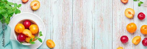 Yellow and red plums in a plate on worn wooden table flat lay, autumn fruits concept, copy space. Web banner, fall harvest background