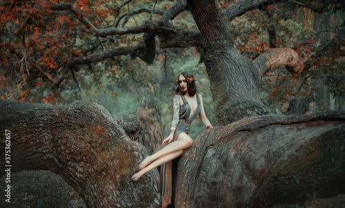 Photo Young beautiful sad woman in the image of the Greek goddess sits on a autumn tree