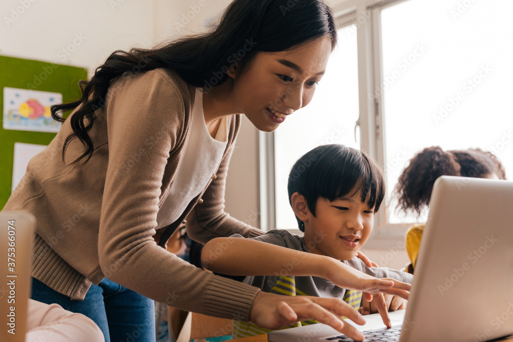 Fototapeta Young adult smiling beautiful Asian teacher helping elementary student boy with laptop in computer classroom. Information Technology class in primary school concept.