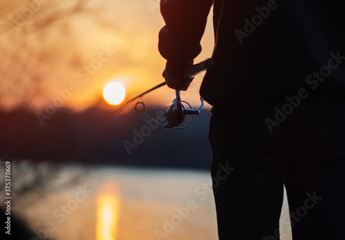 A man on a fishing trip with a spinning rod close-up against the background of t Wallpaper Mural