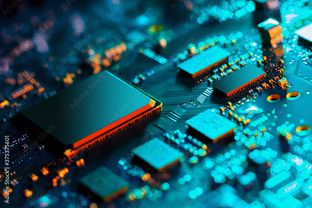 Fototapeta Electronic circuit board with electronic components such as chips close up. Blurry background.