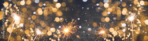 Obraz Silvester / new year background banner panorama long- Golden firework sparklers  in the dark black night with snowflakes snow and bokeh lights - fototapety do salonu