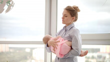 Tired Mother Holding Baby On Hands Near Window. Business Mother Carrying Baby