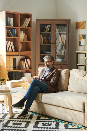 Vertical shot of handsome bearded man in stylish outfit sitting relaxed on sofa in modern office room making notes #375379645