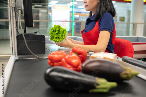 Asian woman wearing red apron sitting at cash desk beeping vegetables Canvas Print