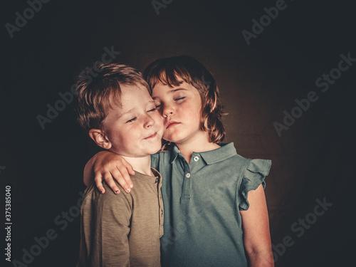 Fotografia preciosos hermanos mellizos rubios divirtiendose en una sesion de fotos de estud