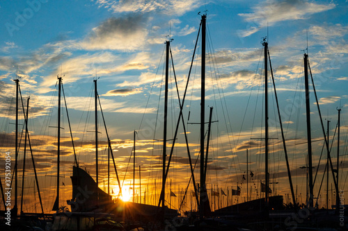 Fotografering silhouettes of boat's mast at sunset in the port of port camargue, France