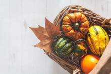 Top View Of Pumpkins In Wicker Basket On Rustic White Wooden Table With Copy Space