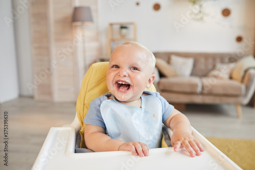 Photo Horizontal portrait of cheerful little child sitting on high chair with food aro
