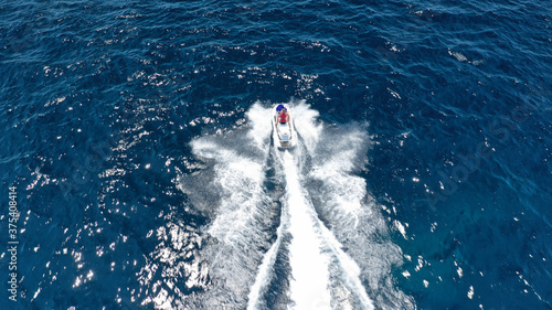 Aerial photo of woman operating jet ski cruising in low speed in deep blue crystal clear waters