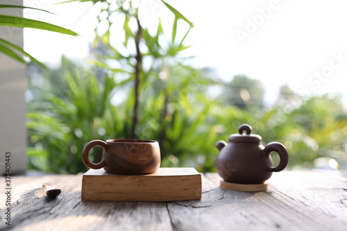 Cuadros en Lienzo Brown wooden cup with traditional clay tea pot with thick old book on wooden tab